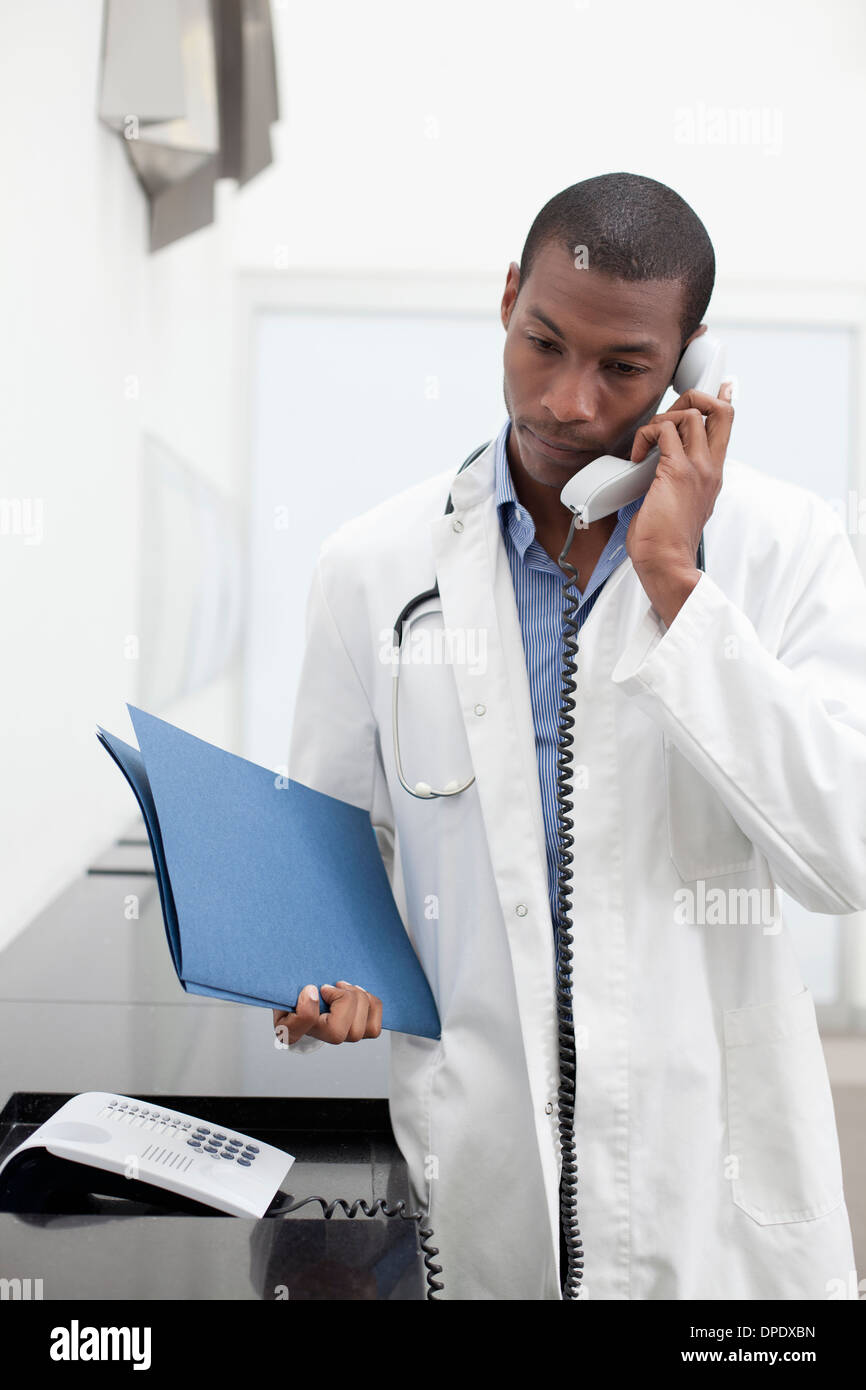 Doctor on telephone call, holding paperwork - Stock Image