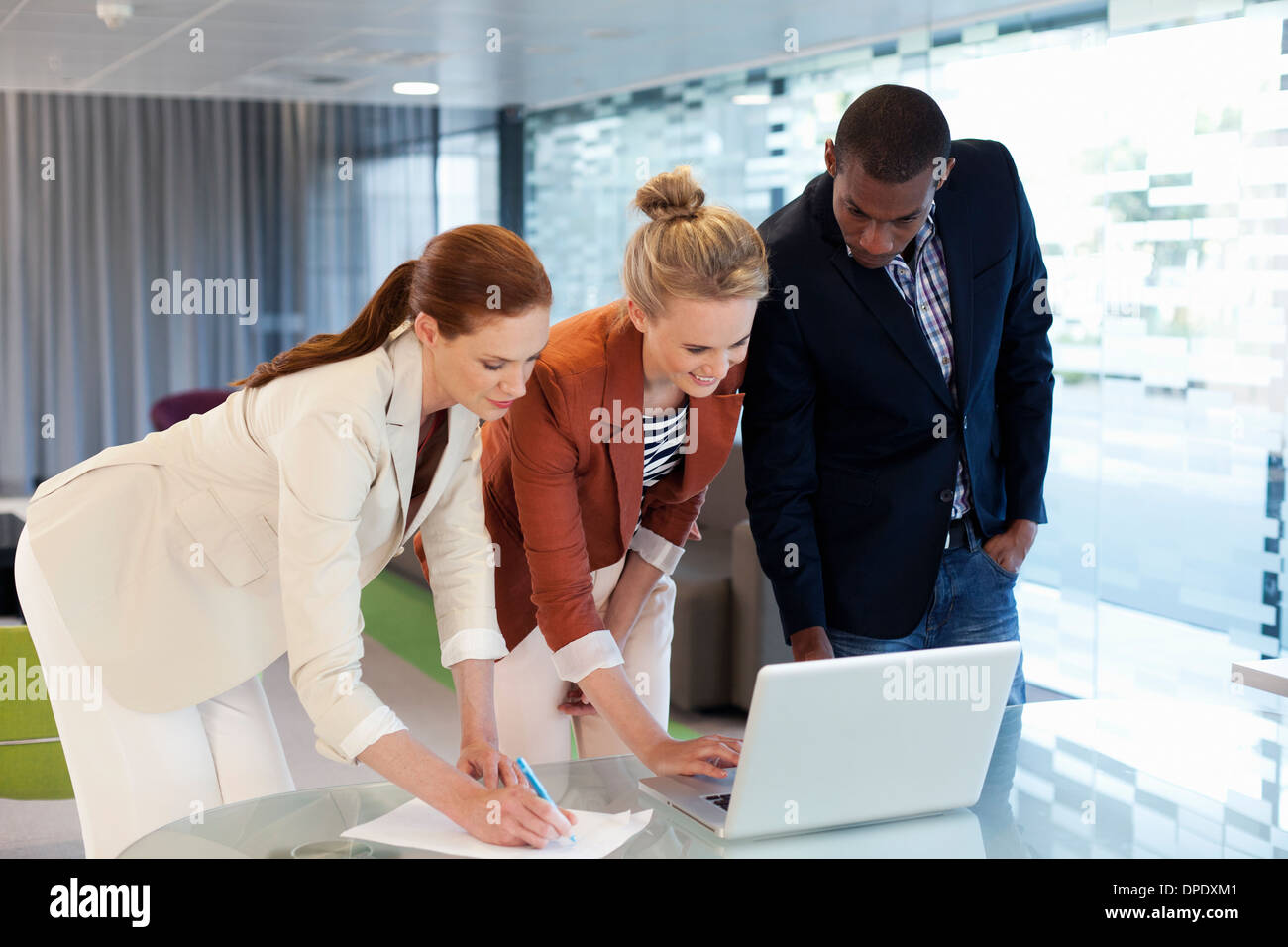 Businesspeople working on laptop and writing activity - Stock Image