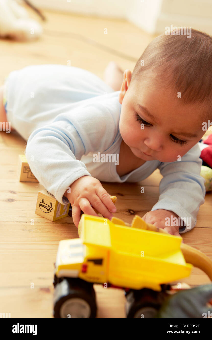 Baby lying on front playing with blocks and truck - Stock Image