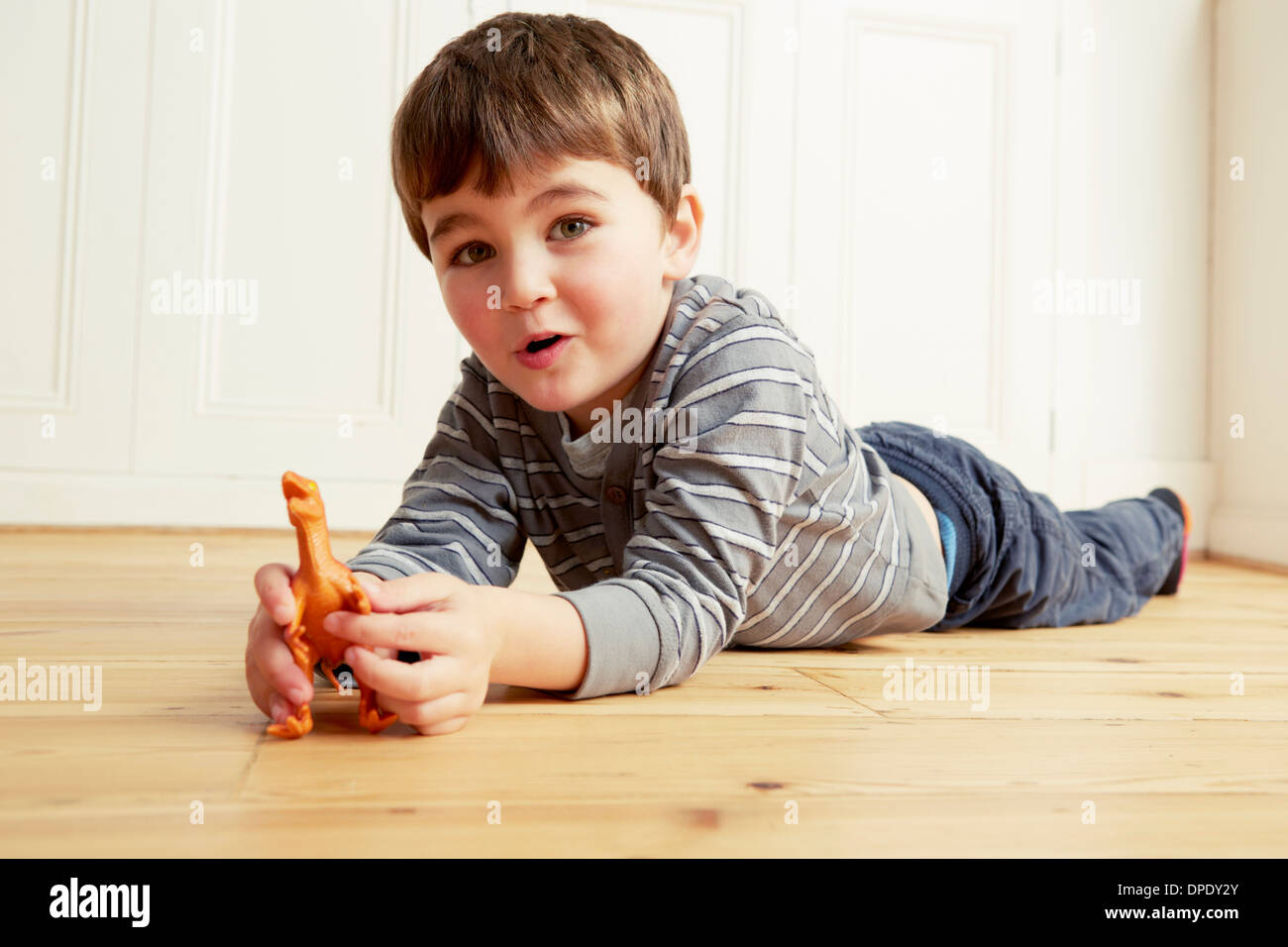 Boy lying on front playing with toy dinosaur - Stock Image