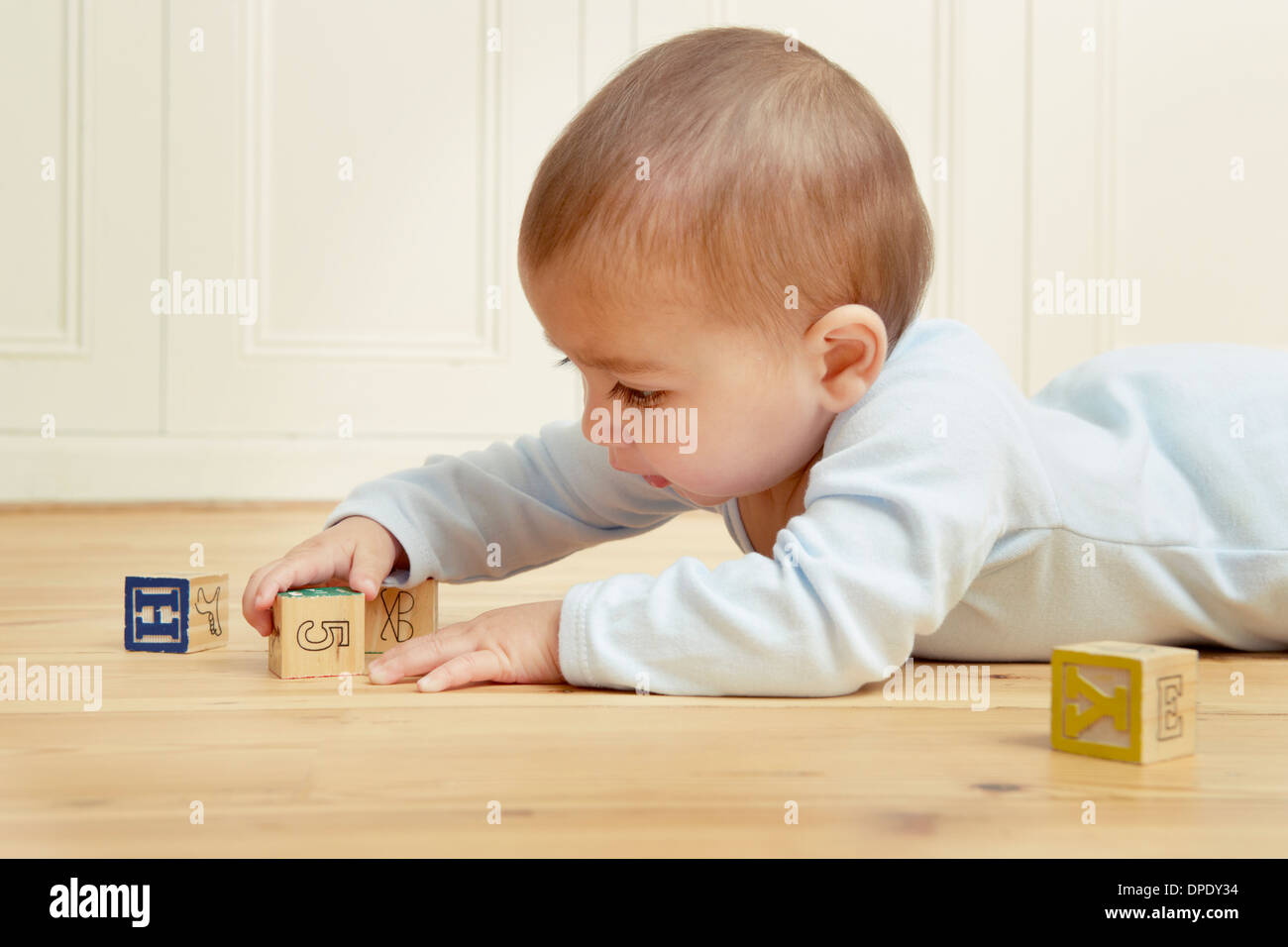 Baby lying on front playing with building blocks - Stock Image