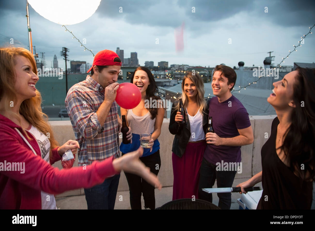 Young adult friends fooling around at barbeque - Stock Image