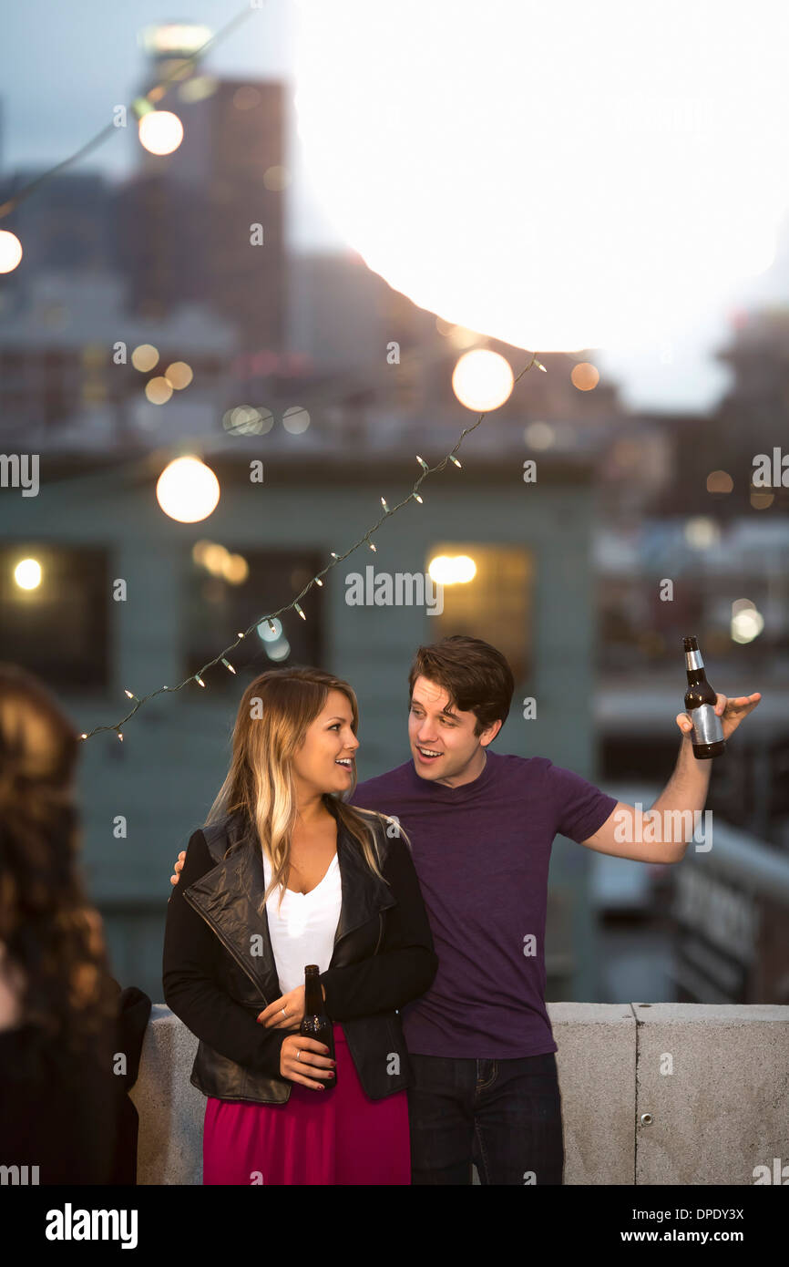 Young couple flirting at rooftop barbecue - Stock Image