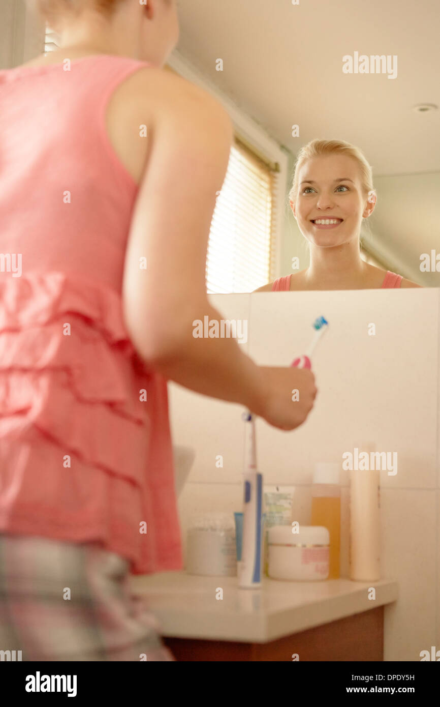 Young woman in bathroom brushing teeth - Stock Image