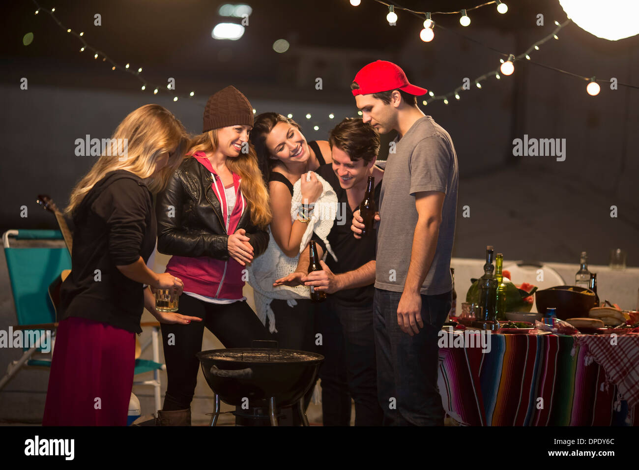 Young adult friends keeping warm at rooftop party - Stock Image