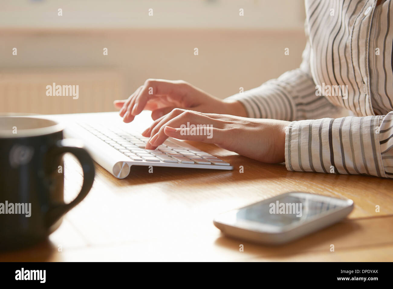 Cropped image of woman typing on wireless keyboard - Stock Image