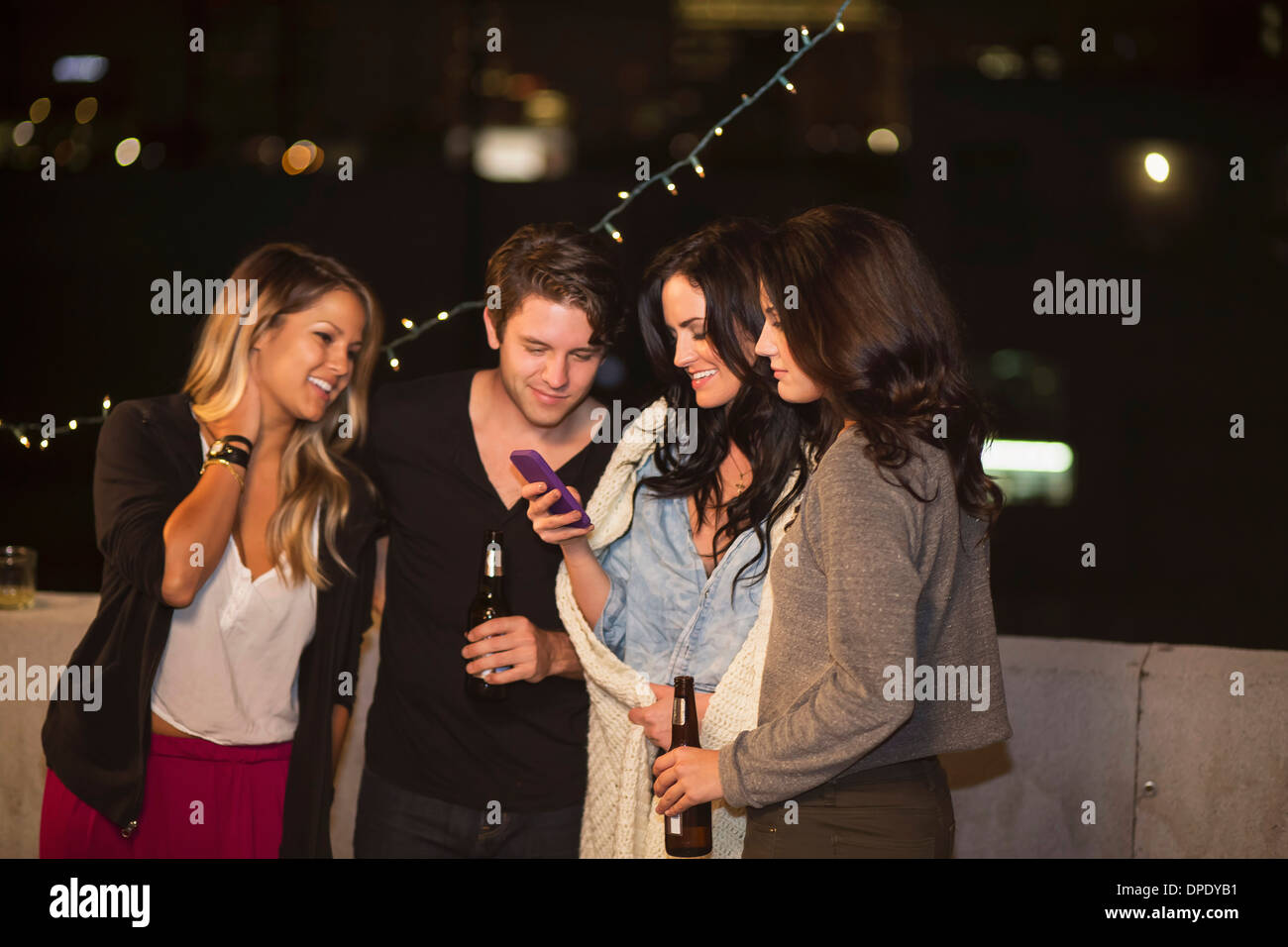 Young adult friends looking at mobile phone at rooftop party - Stock Image