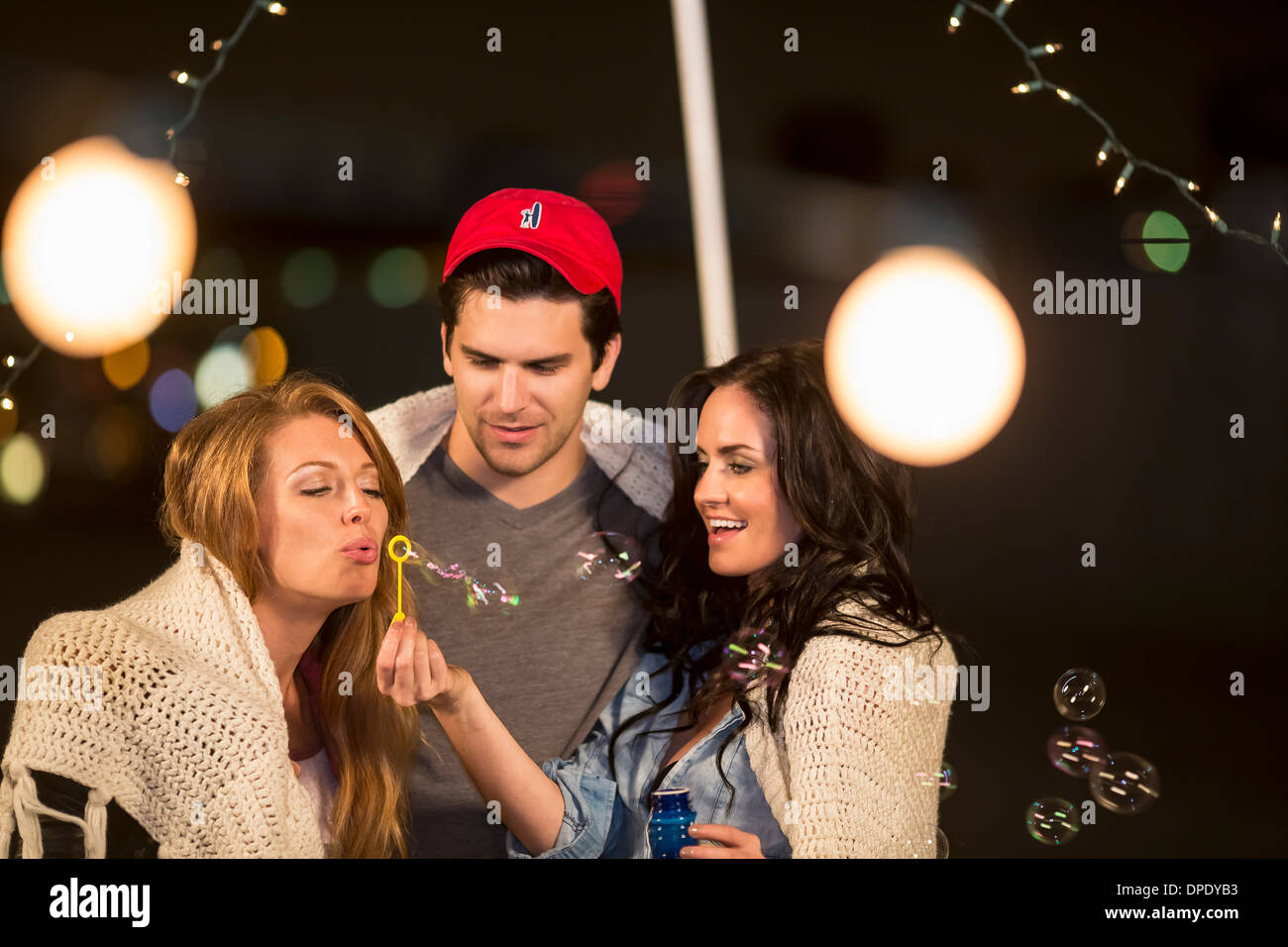 Young adult friends fooling around blowing bubbles at rooftop party - Stock Image