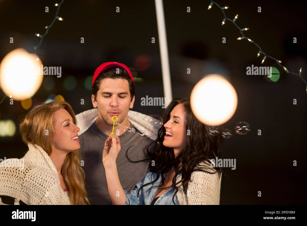 Young adult friends blowing bubbles at rooftop party - Stock Image