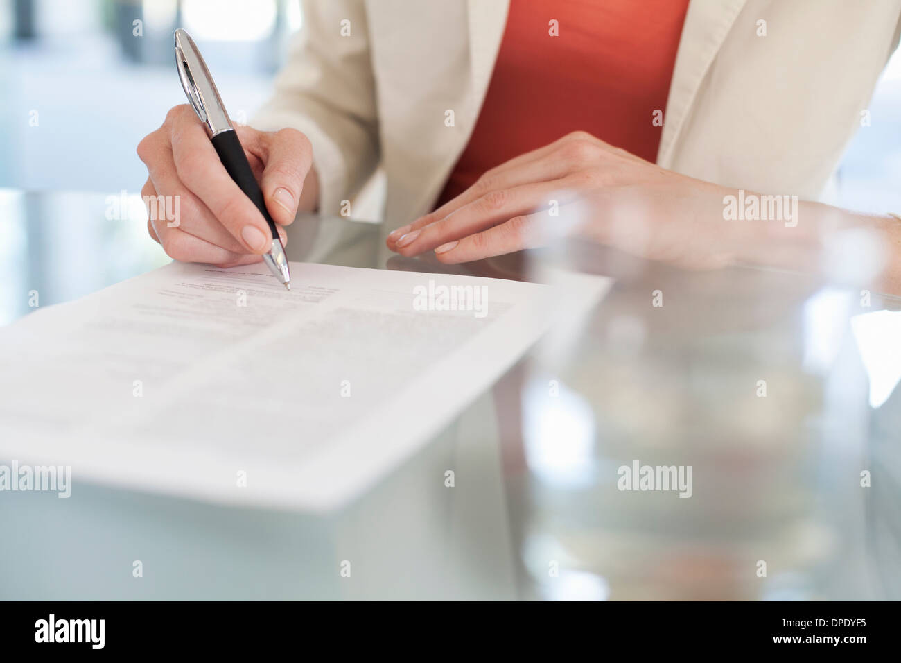 Cropped image of businesswoman signing paperwork - Stock Image