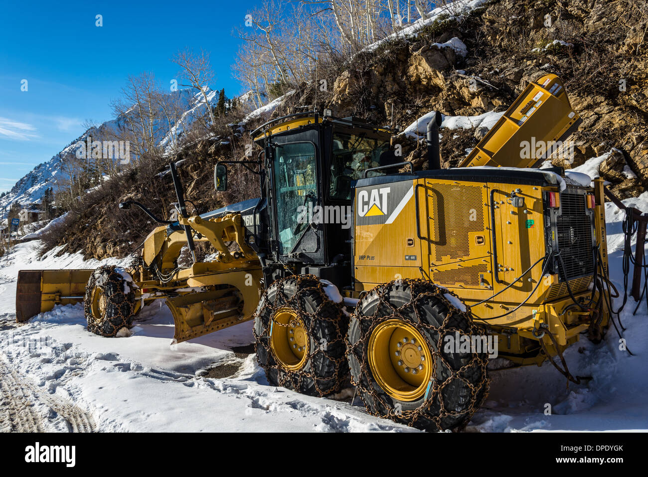 Snowplow with snow chained tires. Alta, Utah, USA. - Stock Image