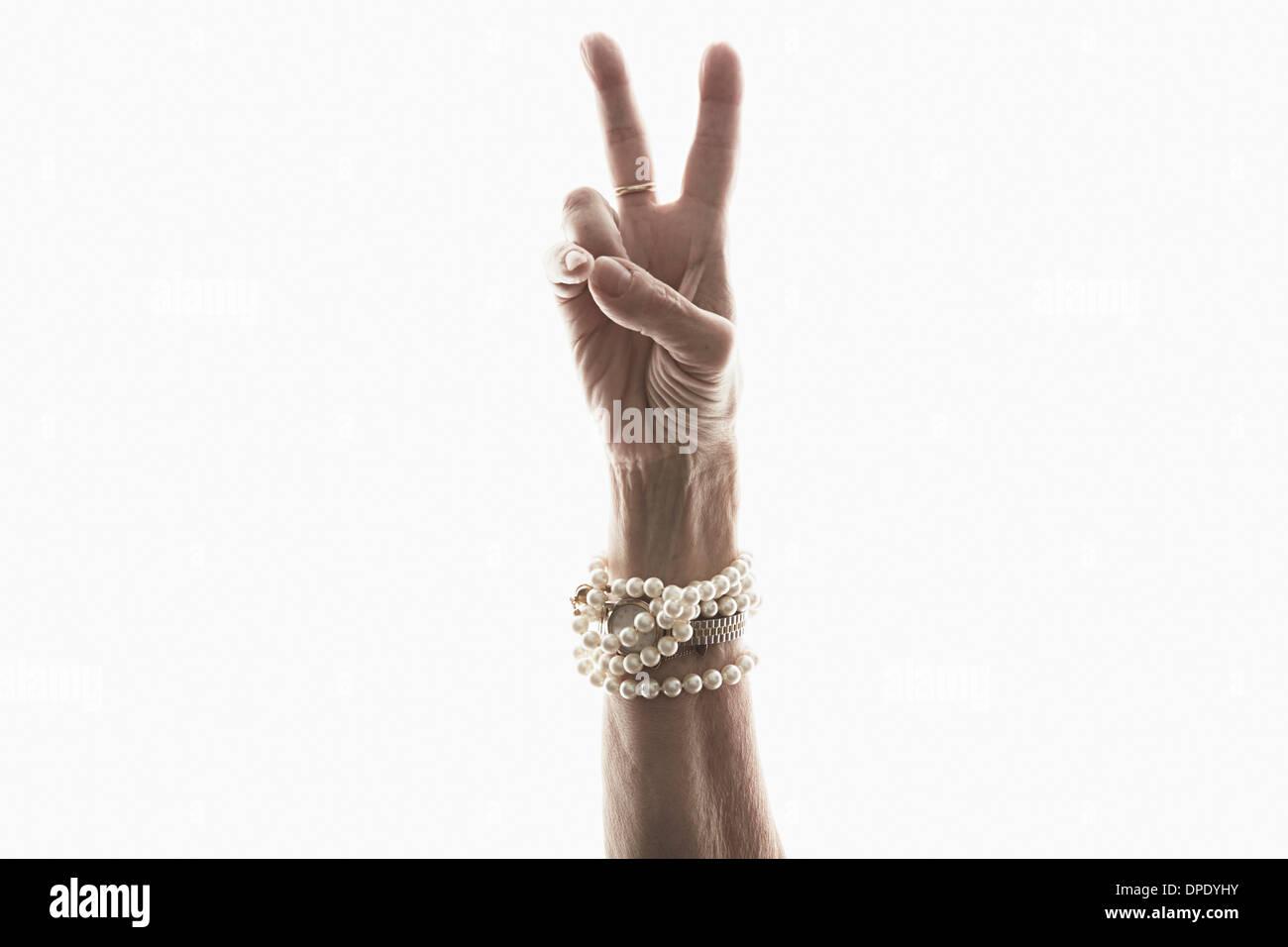Studio shot of mature woman's hand making peace gesture - Stock Image
