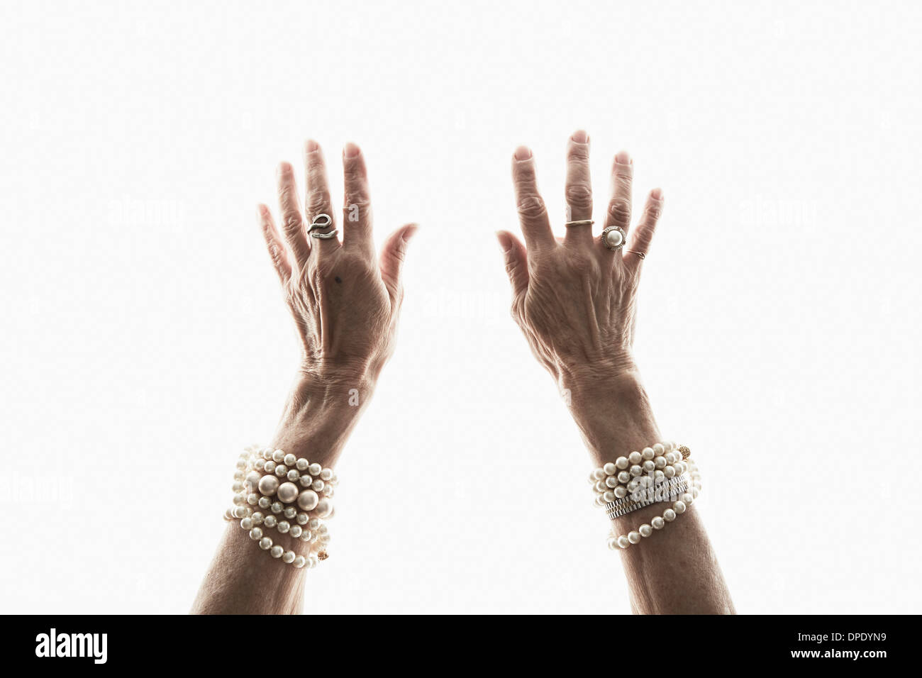 Studio shot of mature woman's reaching hands - Stock Image
