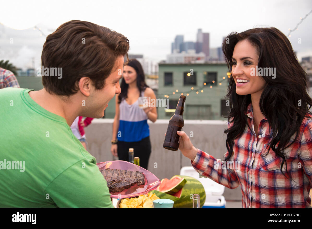 Young couple flirting at barbeque - Stock Image