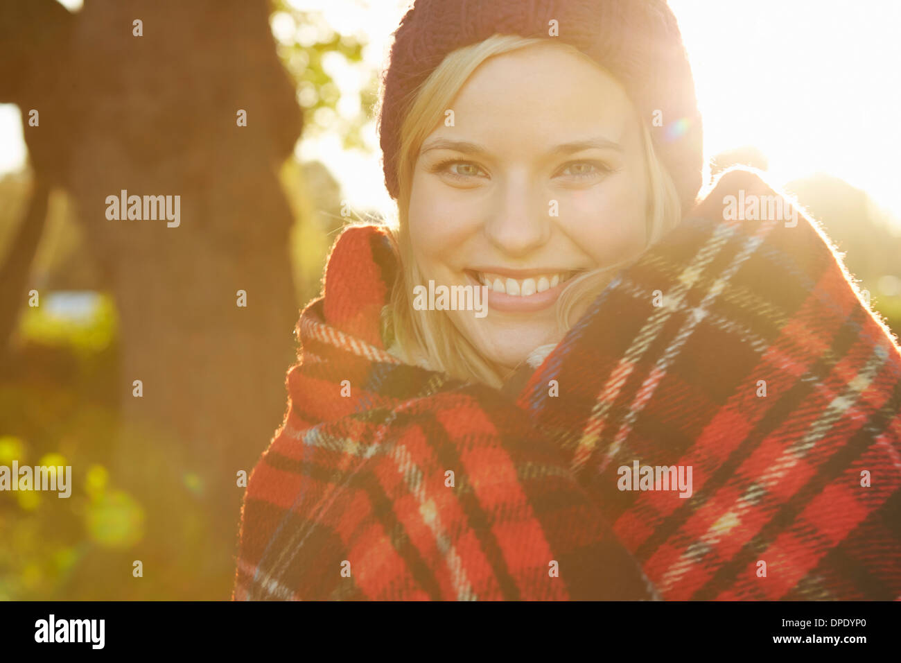 Portrait of young woman in park, tartan picnic blanket around shoulders - Stock Image