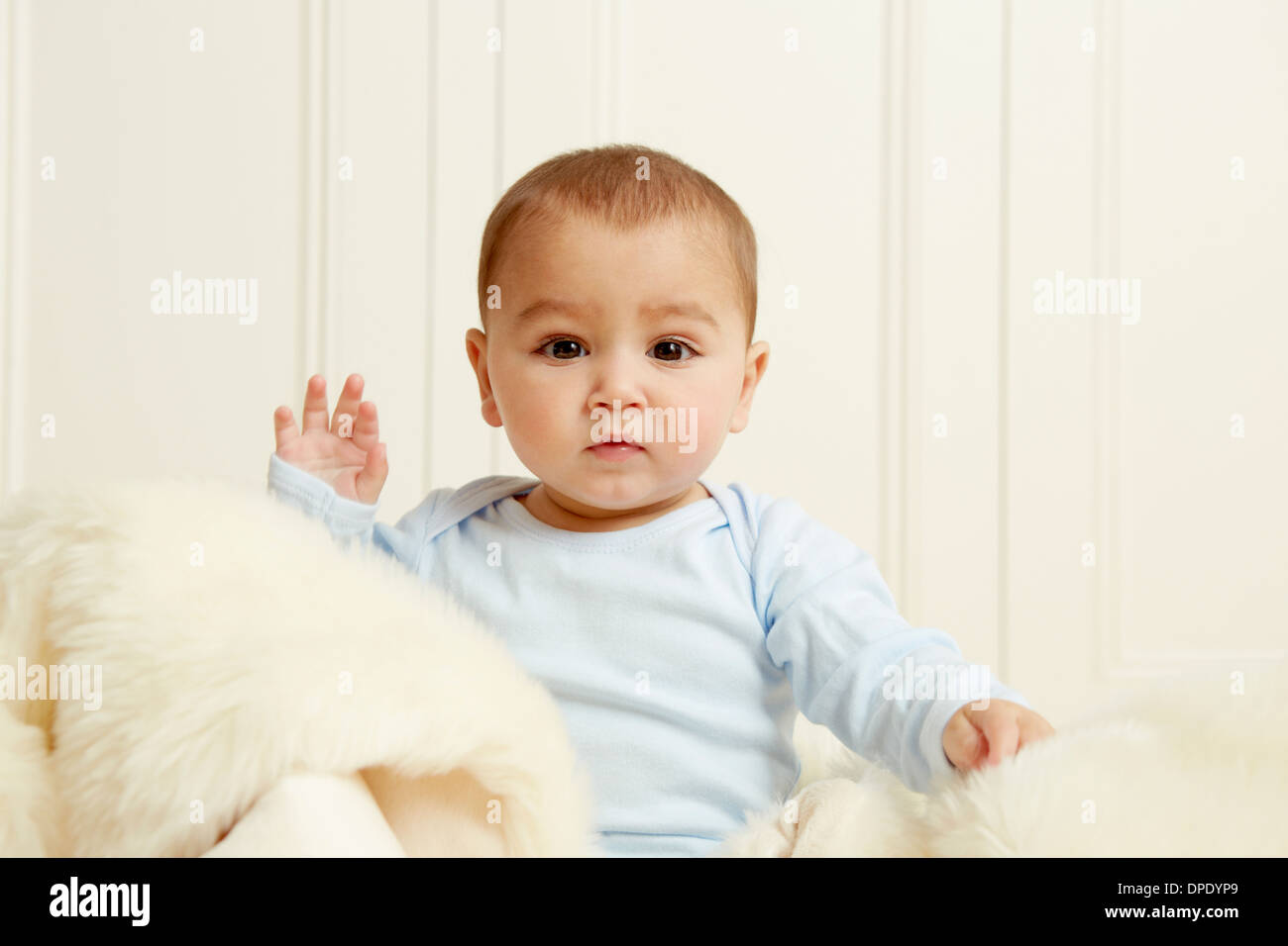 Baby sitting on sheepskin rug - Stock Image