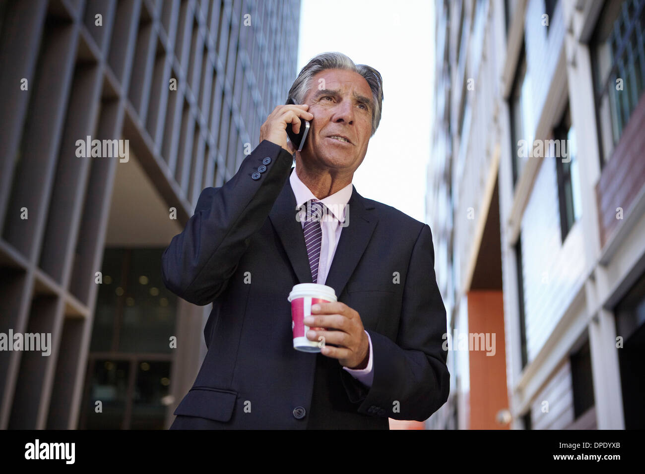 Businessman holding smartphone and hot drink, making phonecall - Stock Image