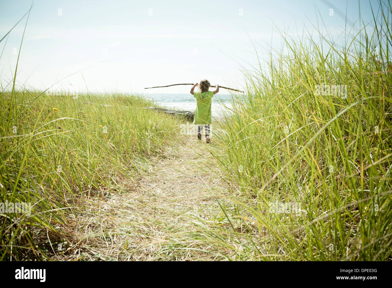 Female toddler carrying long stick Stock Photo