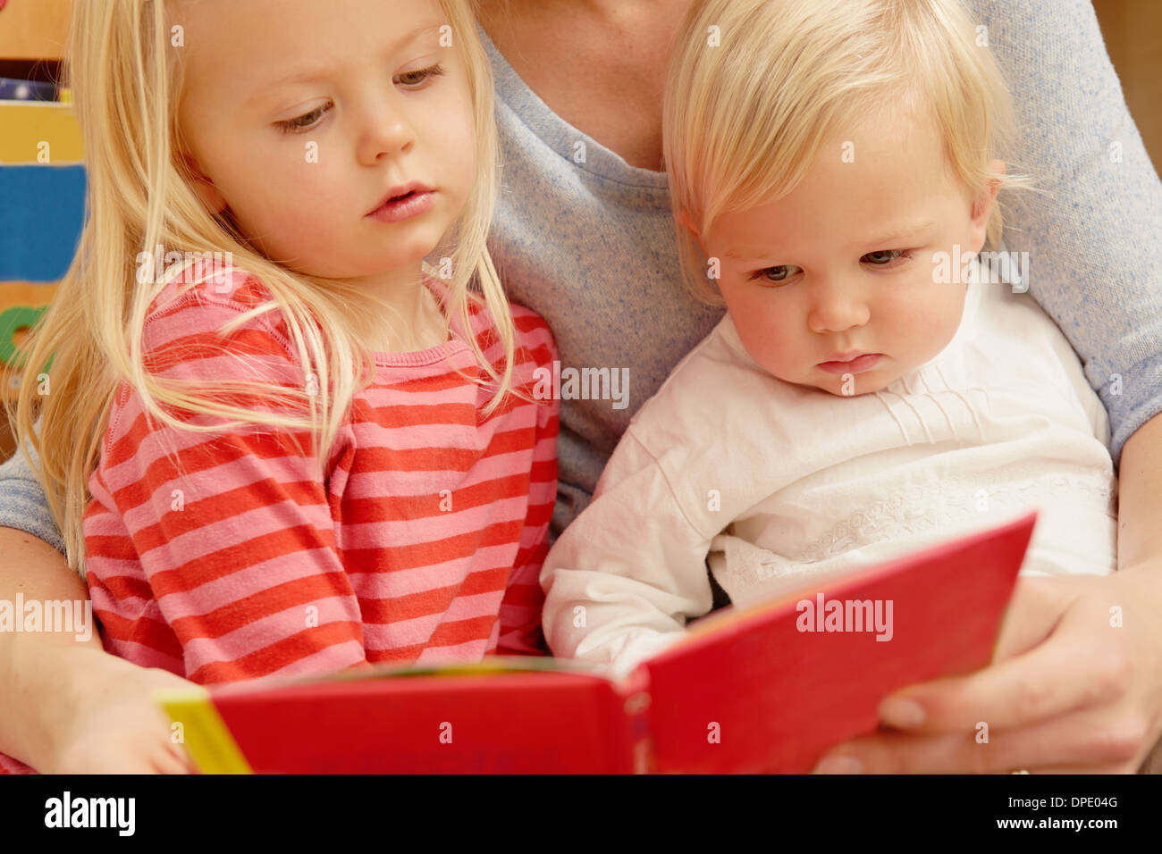 Mother reading picture book with two daughters - Stock Image