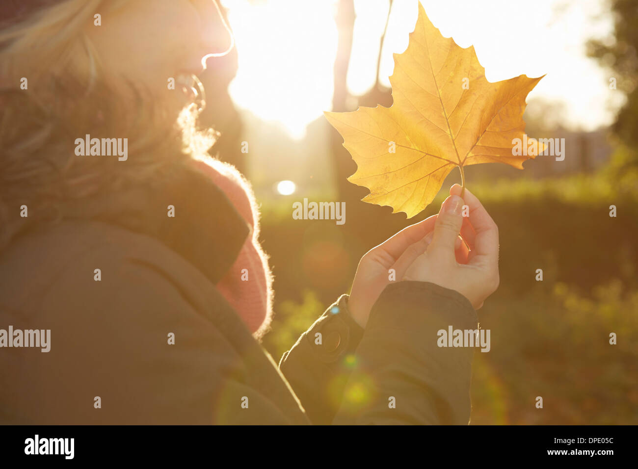 Portrait of young woman in park, holding autumn leaf Stock Photo