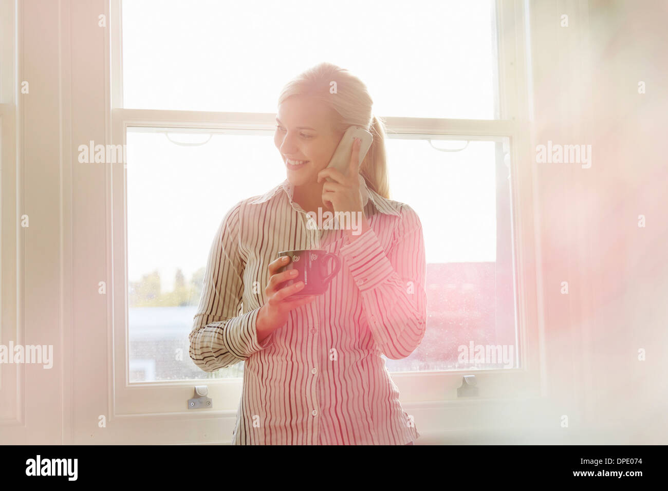 Young woman on phonecall, holding hot drink - Stock Image