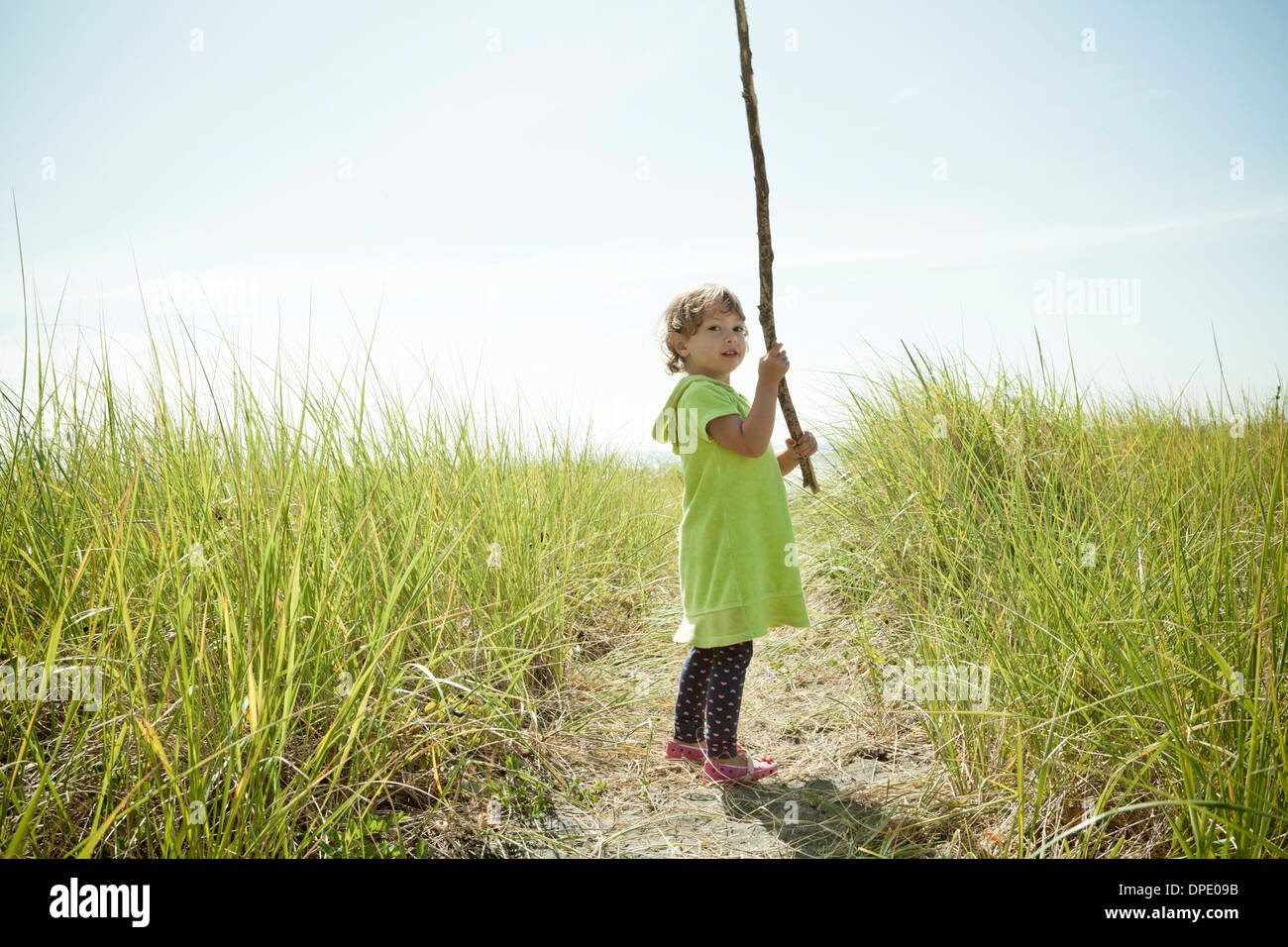 Portrait of female toddler holding long stick Stock Photo