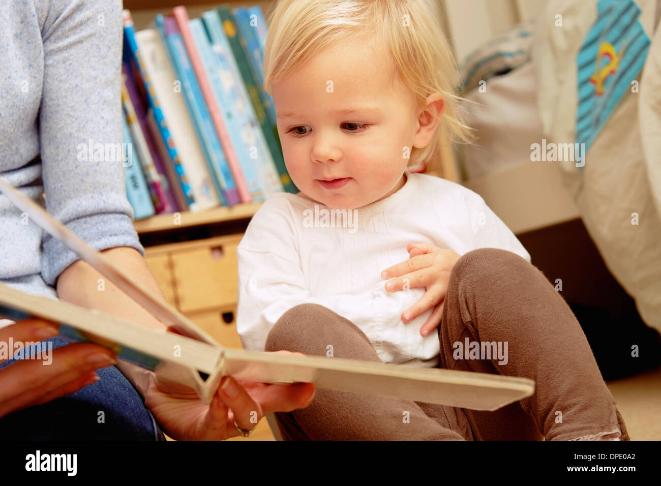 Mother reading picture book with baby daughter - Stock Image