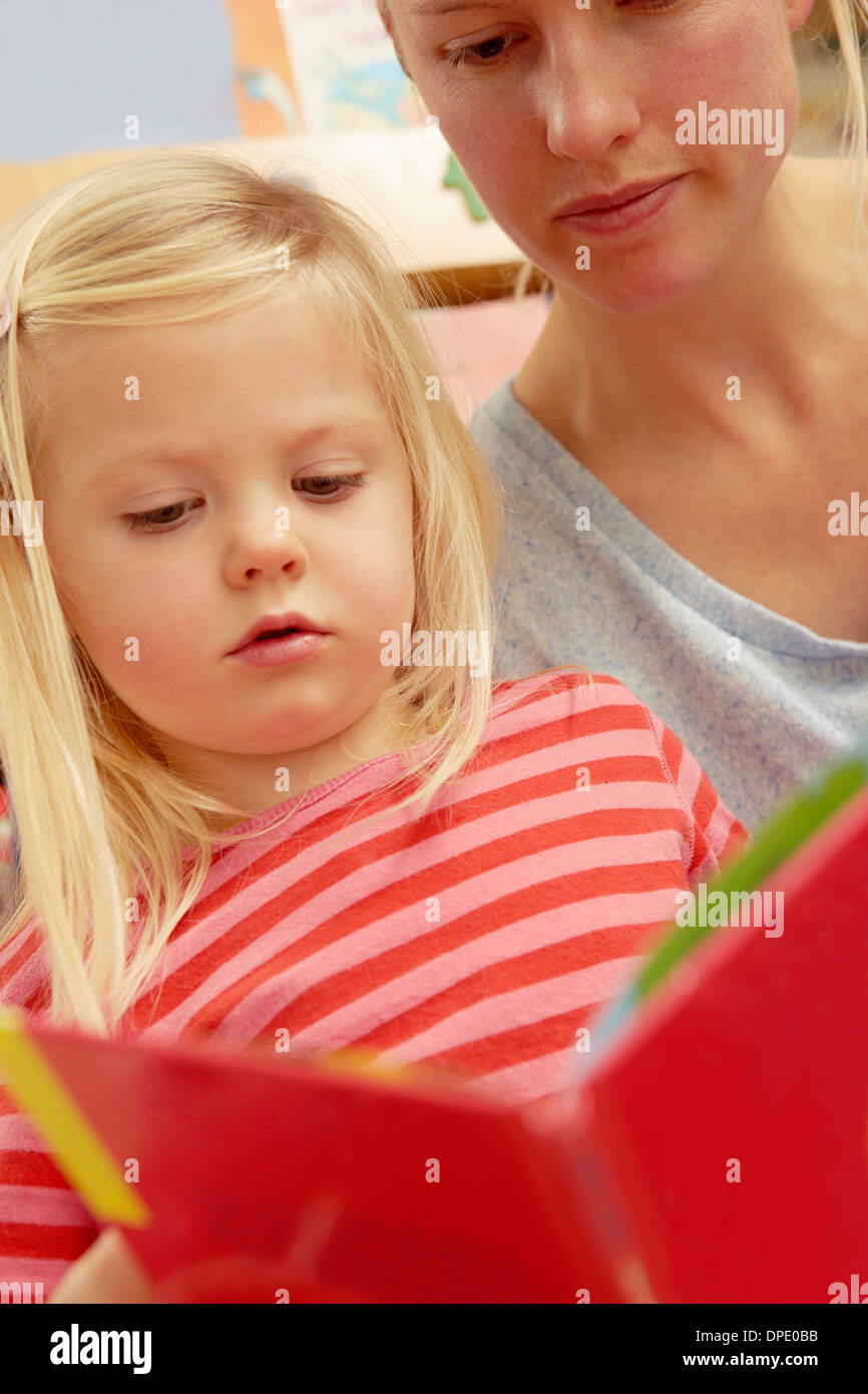 Mother reading picture book with daughter - Stock Image