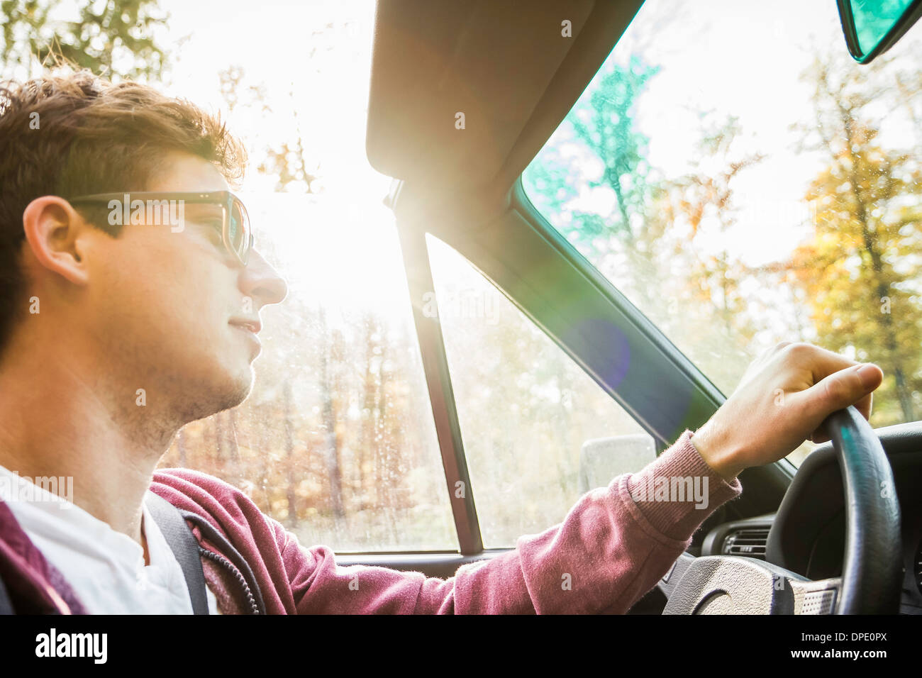 Young man leaning driving convertible on country road - Stock Image
