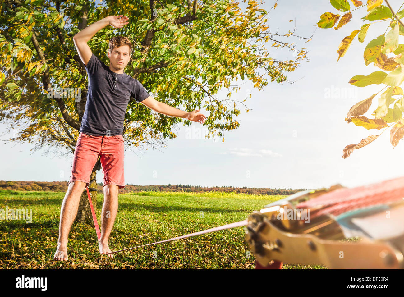 Portrait of young man balanced on slackline - Stock Image