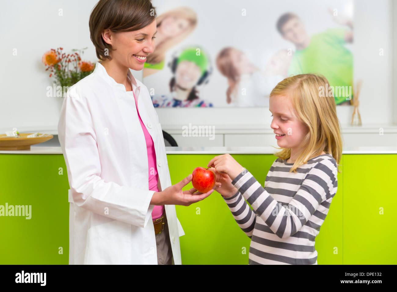 Dentist giving girl apple in dental reception - Stock Image