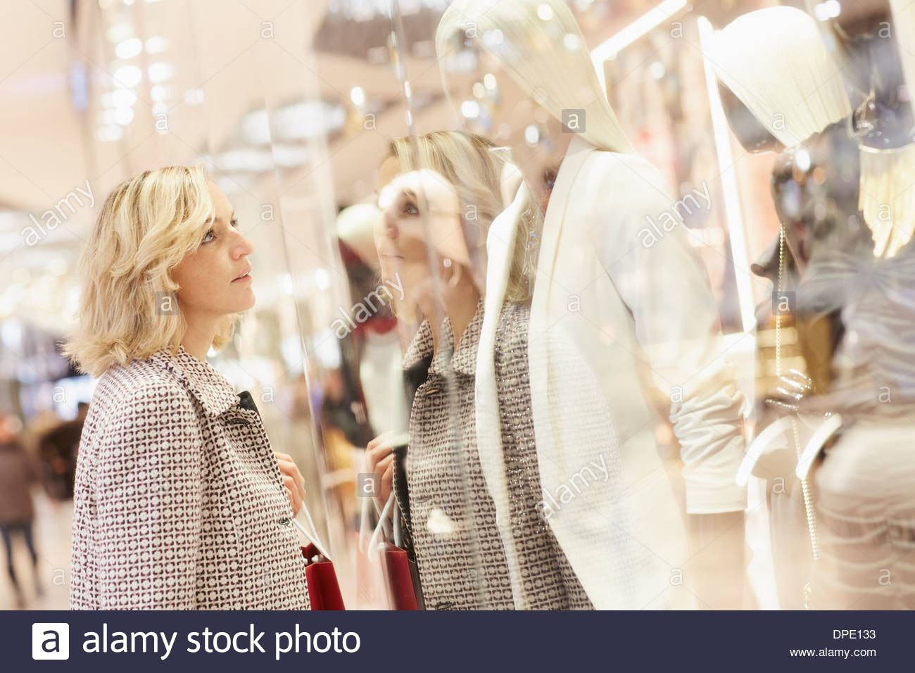 Mid adult female shopper looking at display window in shopping centre - Stock Image
