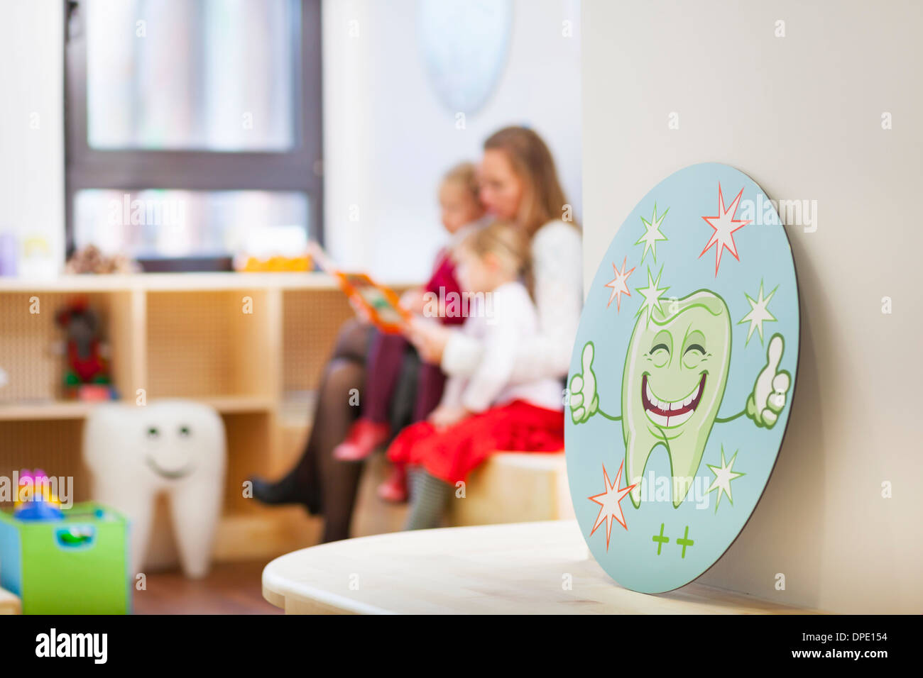 Family in dentists waiting room, picture of tooth in foreground - Stock Image