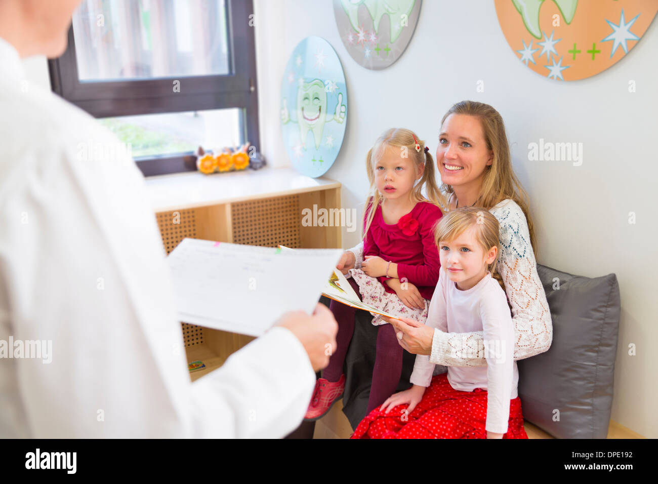 Mother with daughters in dentists waiting room Stock Photo