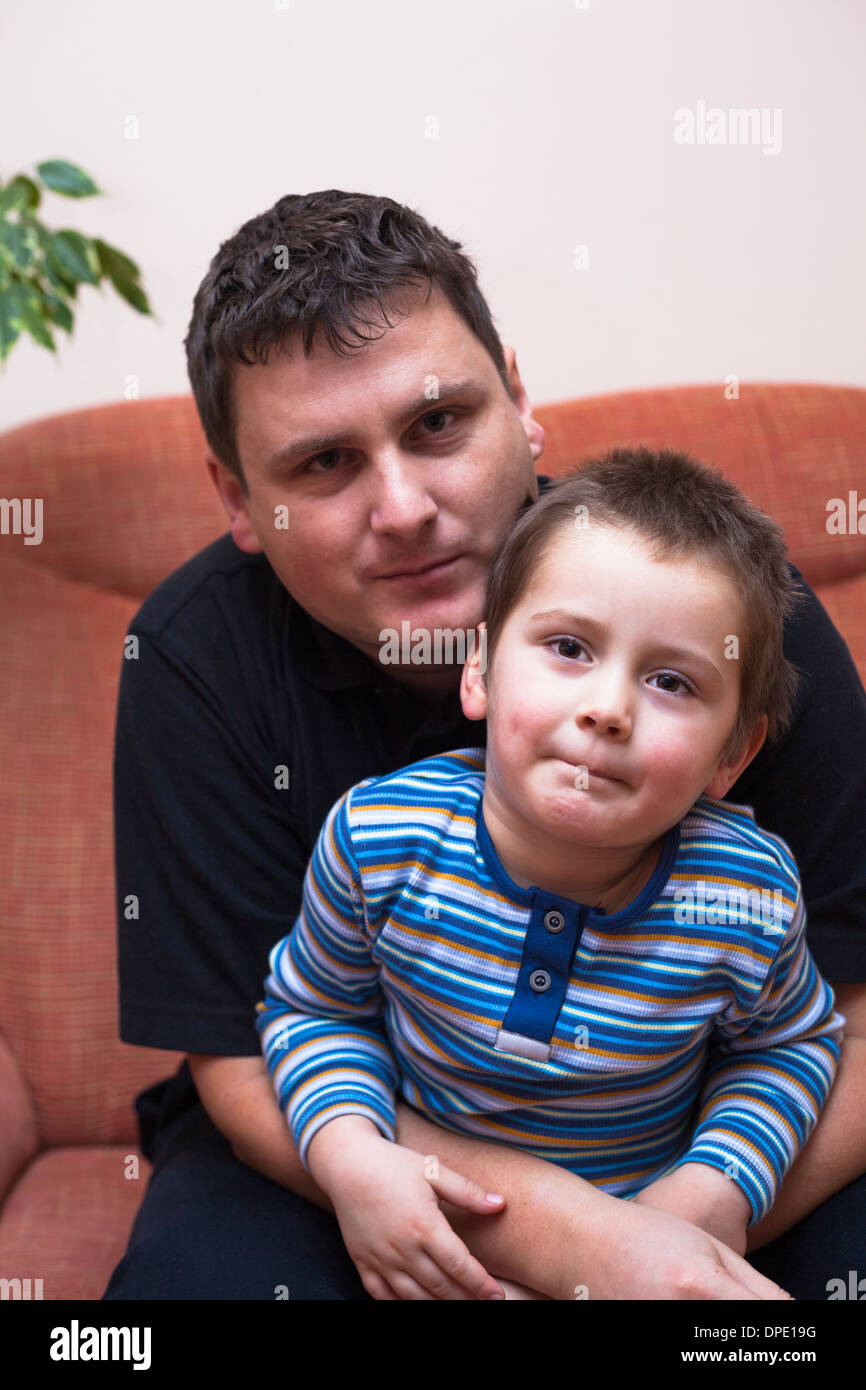 Portrait of father and his child boy, sitting on sofa at home - Stock Image