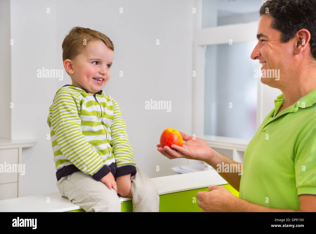 Man giving young boy apple - Stock Image