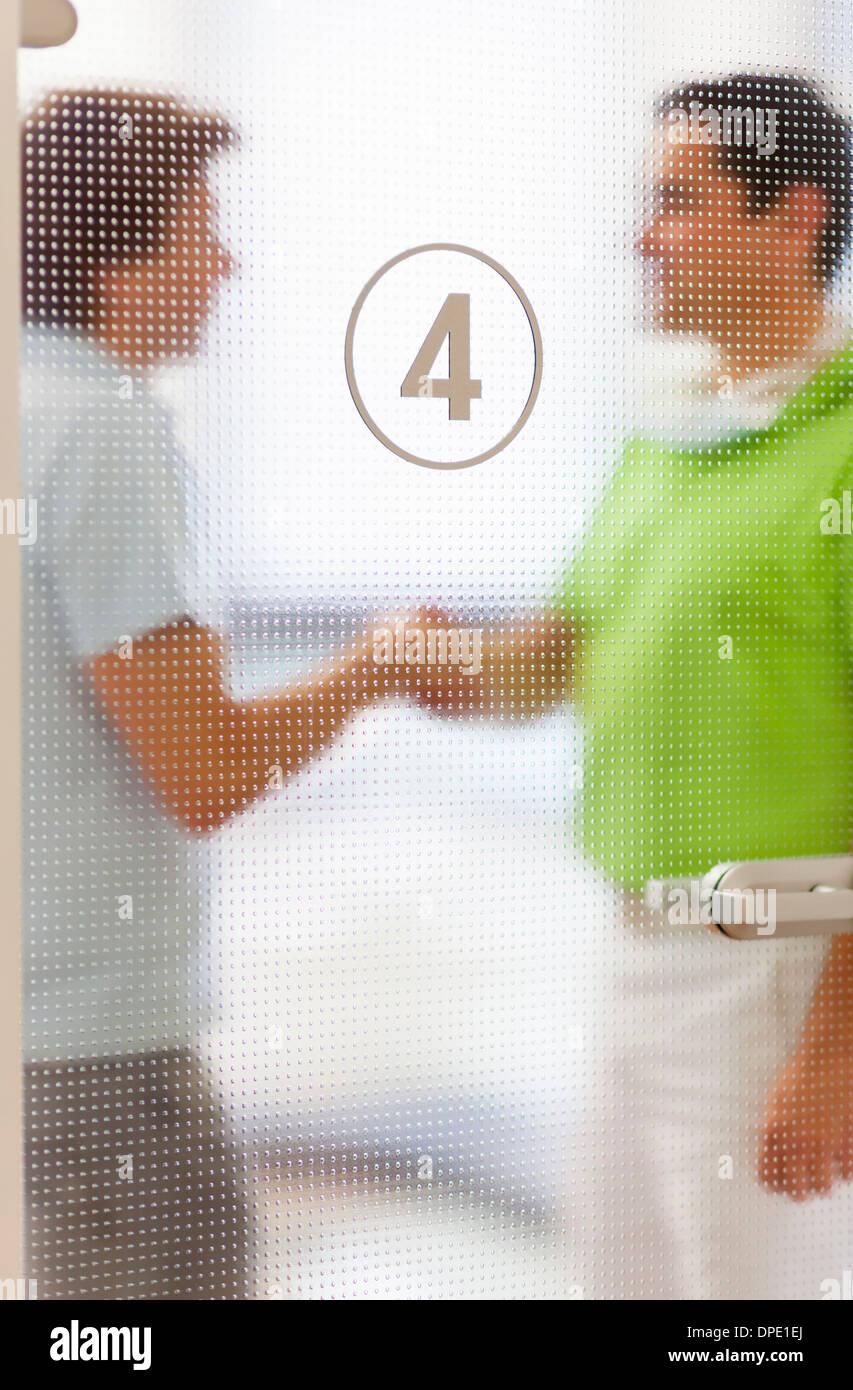 Two men shaking hands behind glass door - Stock Image