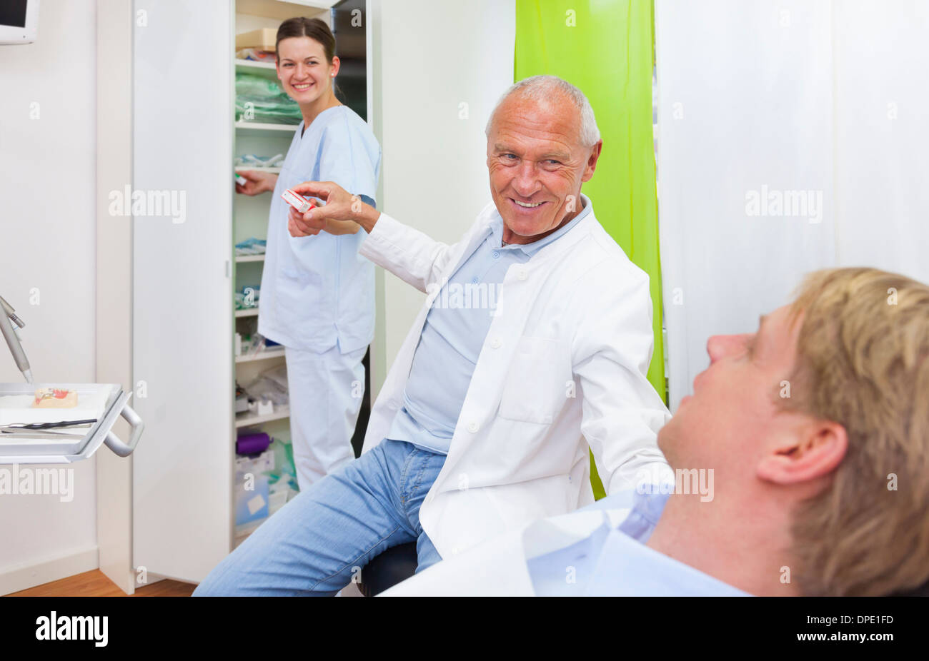 Male dentist treating male patient - Stock Image