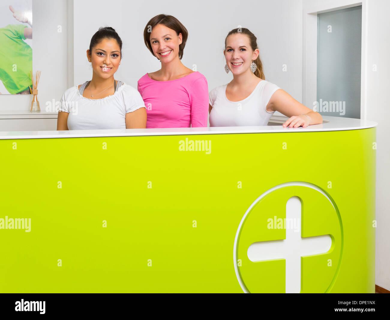 Three female receptionists at desk - Stock Image