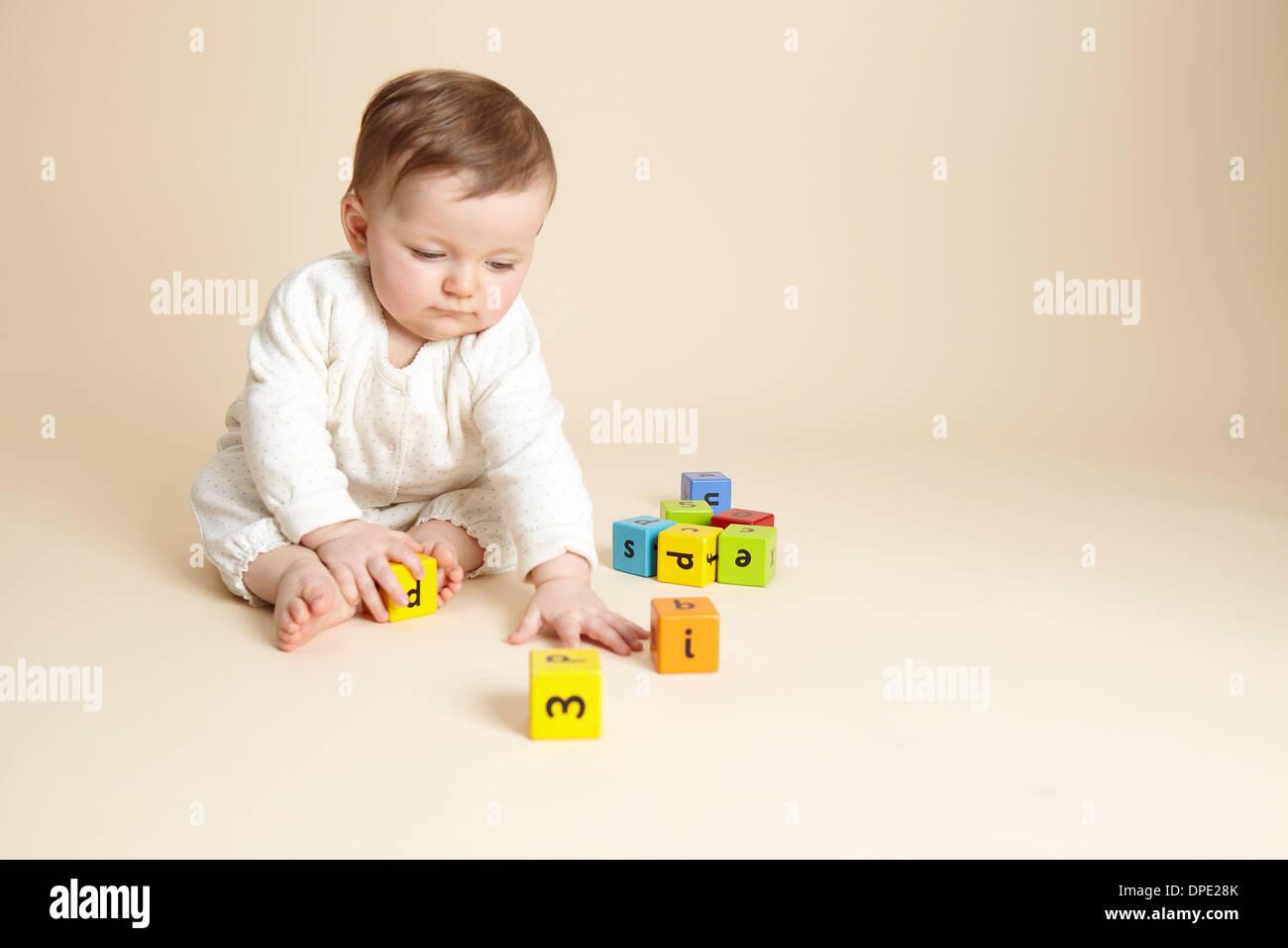 Studio portrait of baby girl playing with alphabet blocks - Stock Image