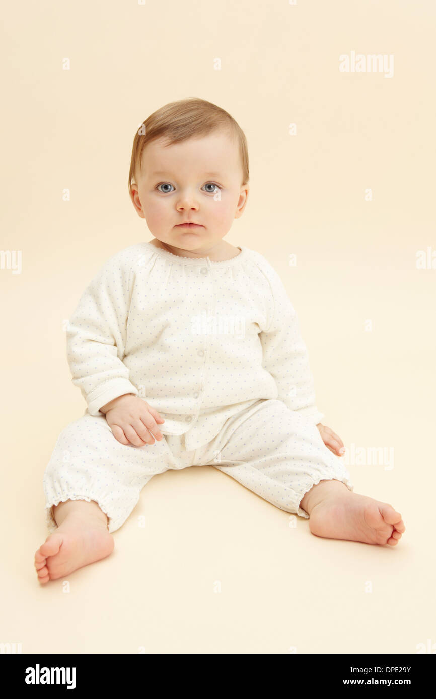 Studio portrait of baby girl staring at camera - Stock Image