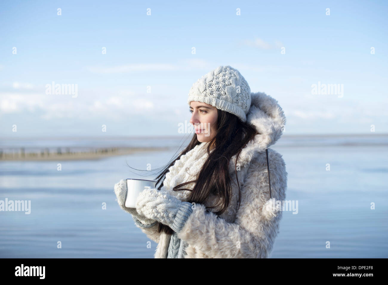 Young woman holding coffee on beach, Brean Sands, Somerset, England Stock Photo