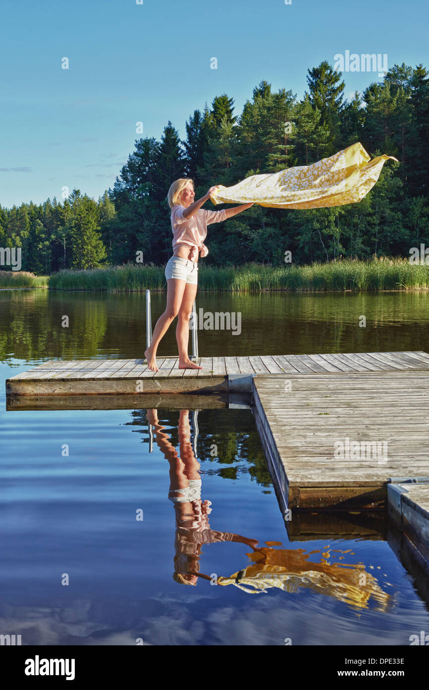 Young woman shaking blanket on pier, Gavle, Sweden - Stock Image