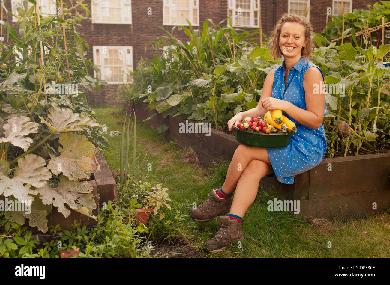 Young woman with harvested vegetables on council estate allotment - Stock Image