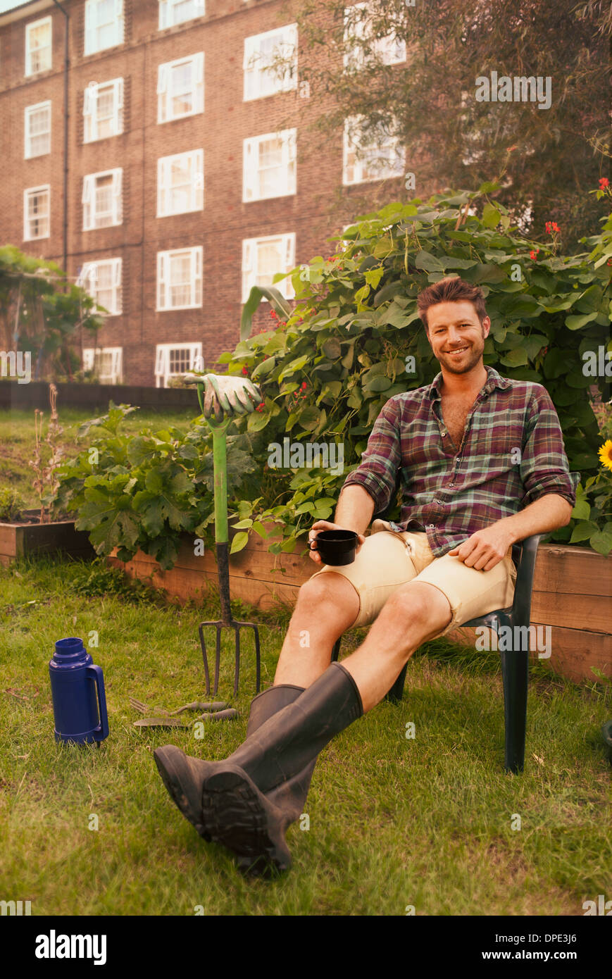 Mid adult man taking a break on council estate allotment - Stock Image