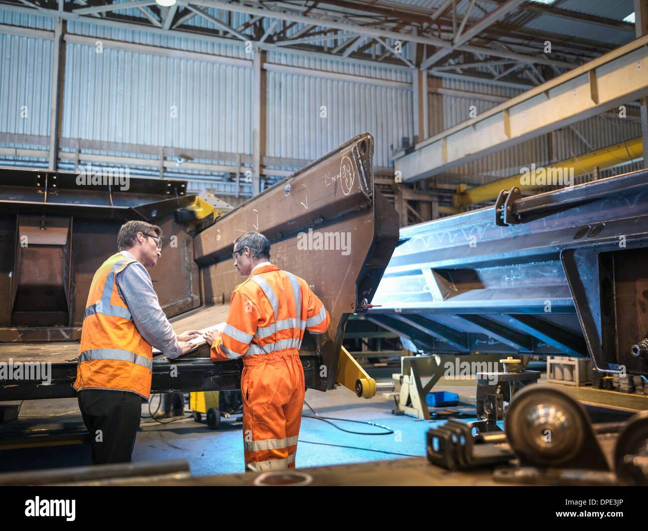 Engineers discussing engineering drawings in factory - Stock Image