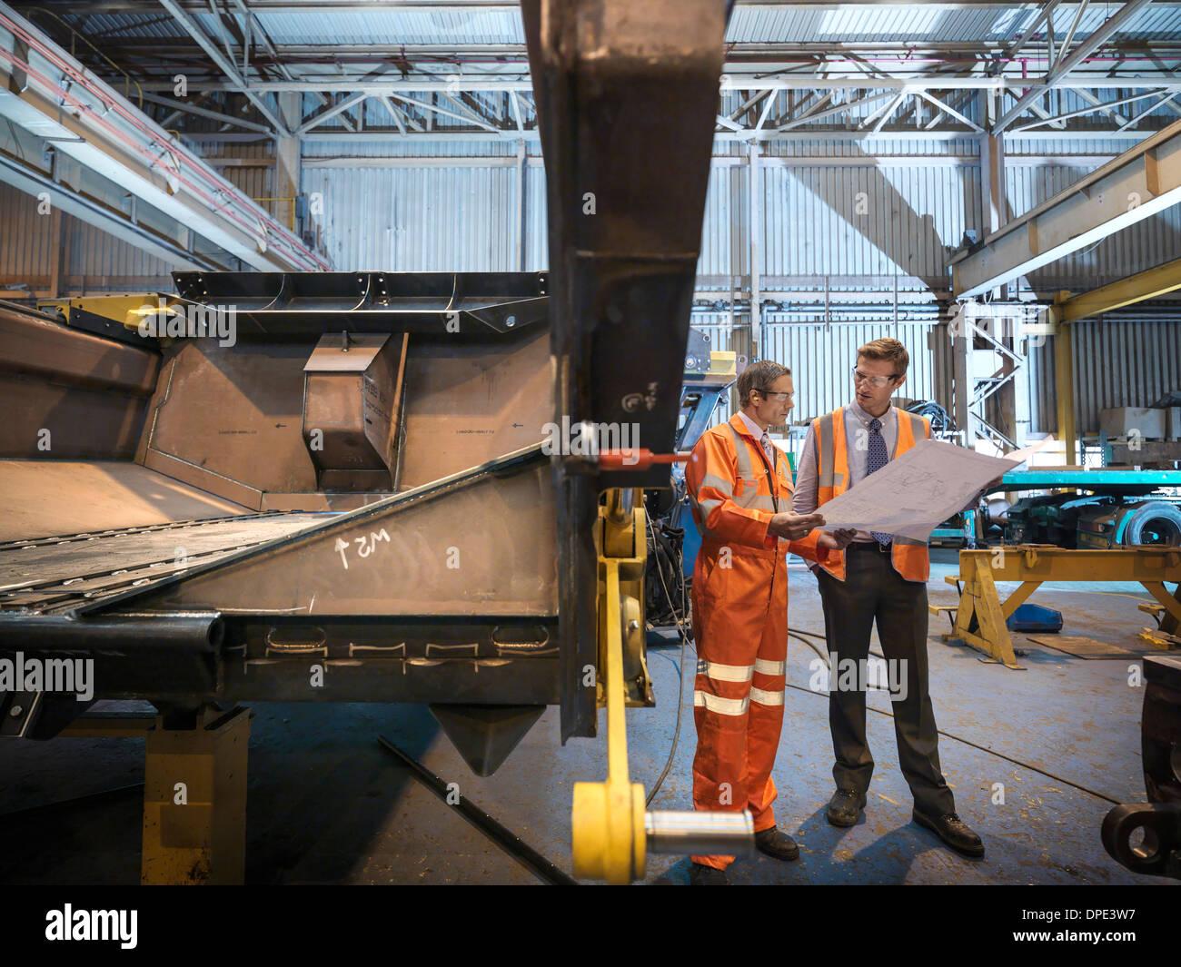 Engineers inspecting engineering drawings in factory - Stock Image