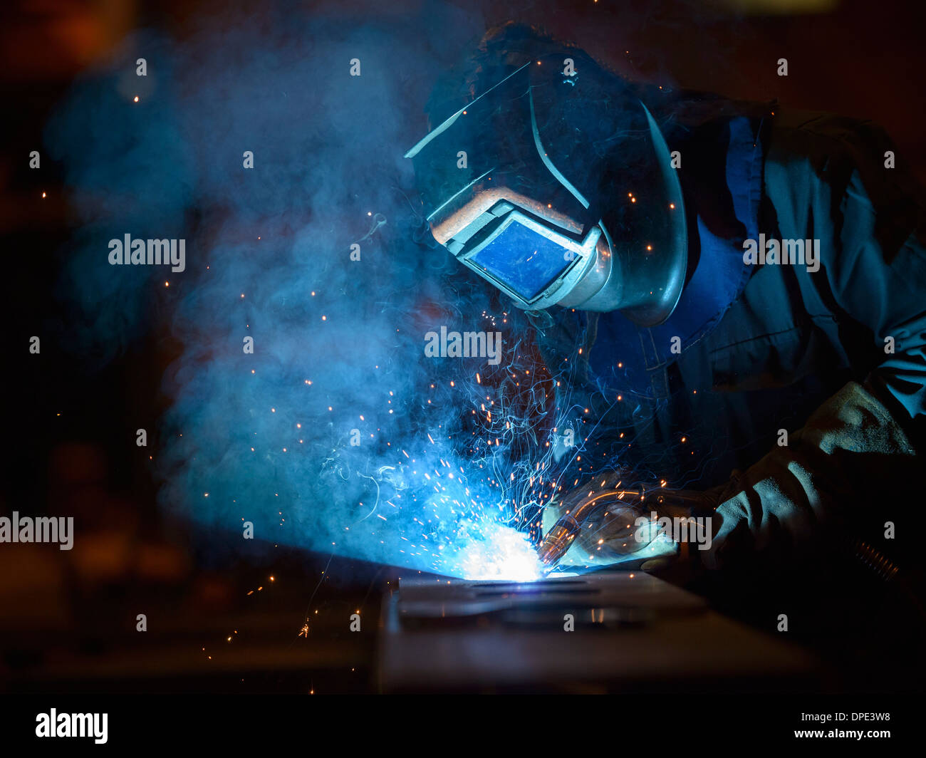 Welder using oxyacetylene torch in factory - Stock Image