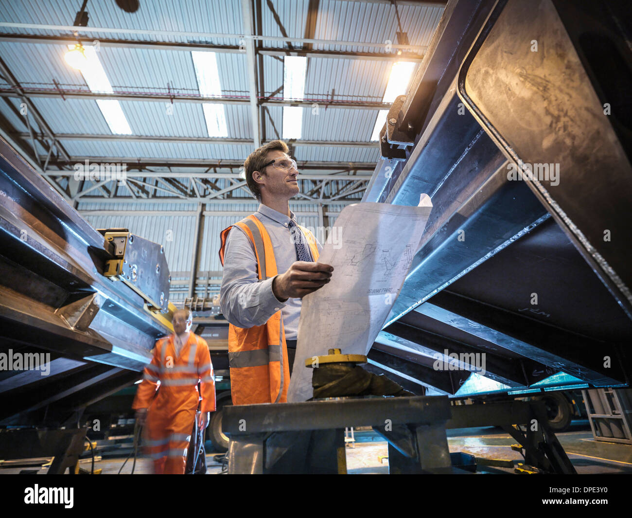Engineer with engineering drawings in factory - Stock Image