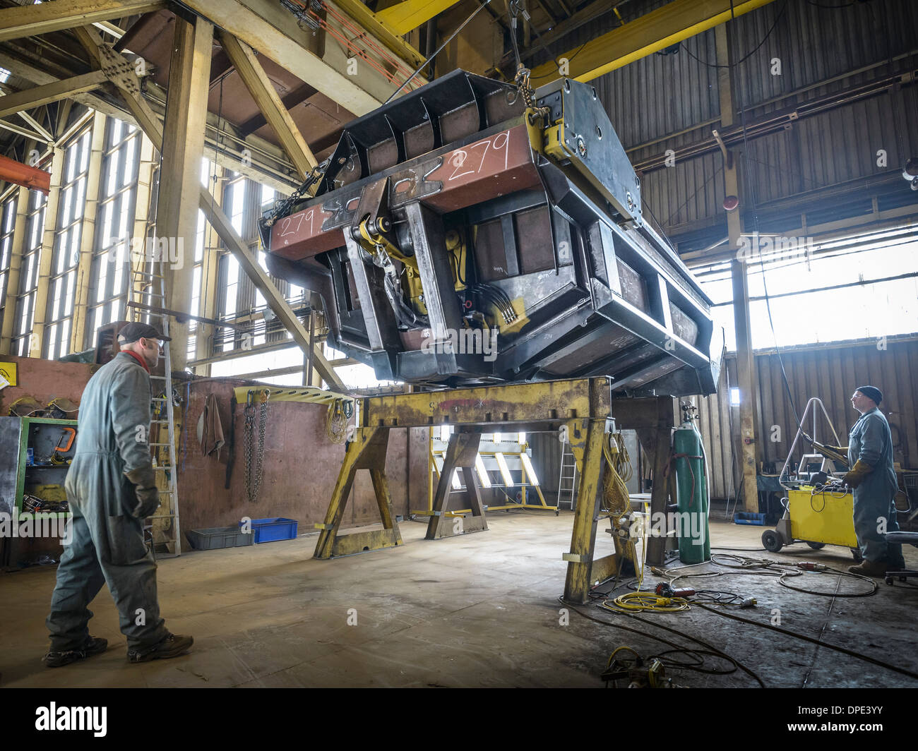Engineers working on steel part in factory Stock Photo